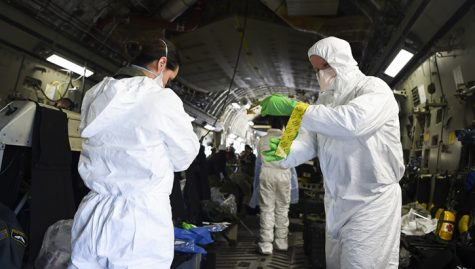 Air men assist each other in putting on their personal protective equipment on-board the Air Force C-17 Globemaster III during transportation isolation training. This system is used to transport patients with diseases such as COVID-19.
