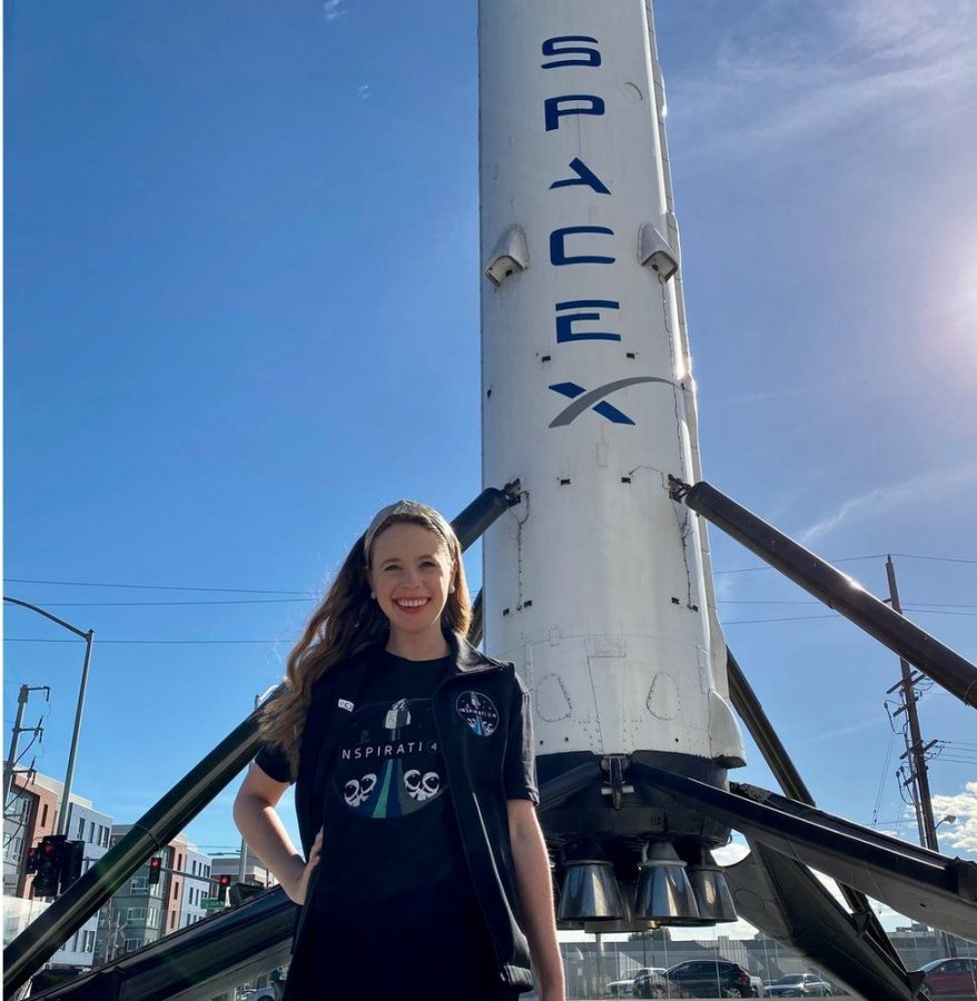 Hayley Arceneaux standing in front of a mock-up of the rocket that will carry her to space. Credit: BBC