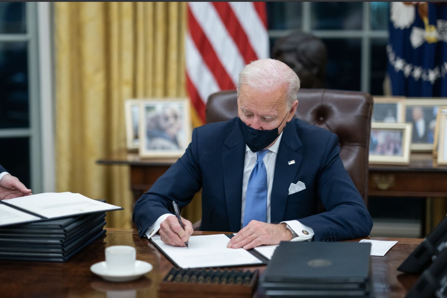 Joe Biden in White House Oval Office signing executive orders.