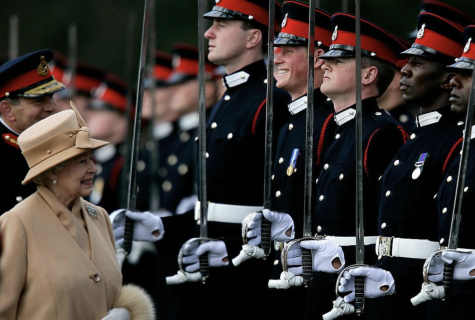 Queen Elizabeth II smiling at Prince Harry Saluting her In Uniform